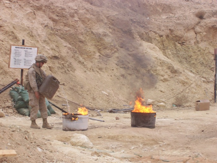 Some poor kid burning a field head (latrine) in Haditha, Anbar Province, Iraq. Dec 2006