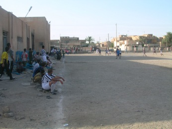 Iraqi men play soccer on a pitch in Sadr City, Baghdad, May 2004.
