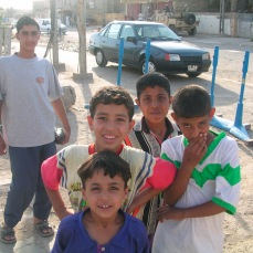 Boys in Sadr City, Iraq, Spring 2004. By the time our occupation ended, seven years later, many of these boys would, if they had survived, been part of the Mahdi Army. Note the open top Hummvee at the top of the photo.