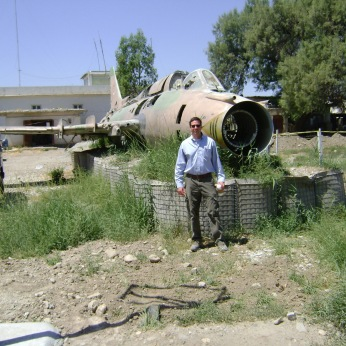 At Jalalabad Airbase in northeastern Afghanistan, Spring 2009. An old Soviet warplane lays broken, placed upon American HESCO, while nearby are the steps where Osama bin Laden announced his arrival in Afghanistan and declared continued war against the US. Bin Laden made that statement several months before the Taliban conquered this area; the Taliban effectively inherited bin Laden. Meanwhile, the man who actually brought bin Laden to Afghanistan, Abdul Rasoul Sayaf is today a prominent member of the Afghan Parliament who has run as a candidate for President. He actually won Kandahar Province in voting in 2014.