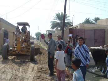 Boys watch a grader at work in a town in Salah ad Din Province, Iraq. These boys are all fighting age now.