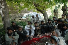 Afghan villagers endure our speeches and await our paying a family for killing their sons.